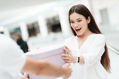 Man and woman in shopping mall. Man presents woman with new round box. royalty free stock photography