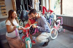 Man and woman shopping new bicycle for little girl in bike shop. Man and women shopping new bicycle for happy little girl in bike shop royalty free stock images