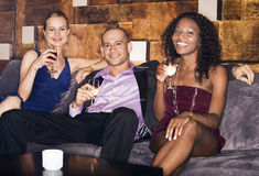 Man With Women Sitting On Couch In Bar Stock Photo