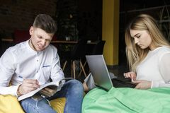 Man and woman are sitting together on soft chairs. Girl is holding laptop on legs. Guy has journal and pen. They are working. Man and women are sitting together stock images