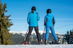 Man and woman skiers on mountain top enjoying landscape. Man and women skiers standing on mountain top together enjoying beautiful mountain landscape on a winter Stock Image