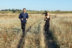 Man and woman in sportswear running in field. Man and women in sportswear running in field. Two young athletic people engaged in sports. Fitness girl and guy royalty free stock image