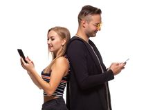 Man and woman stand with their backs to each other with telephones in their hands on white background. Man and women stand with their backs to each other with stock photography