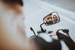 Man And Women Stare In A Bike Rearview Mirror. Bikers Concept. Going For Ride. Fashion Riders. Confident Staring. Speed Vehicle. Biker With A Beard. Motorbike stock photo