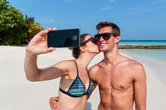 Happy young couple taking a selfie, tropical island and clear blue water as background. Girl kissing his boyfriend stock photo