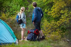 Man and woman tourists backpackers looking for way on trip while stock images