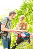 Hiking backpacking couple reading map on trip. Man and women tourists backpackers reading map on trip while resting.  Young couple hikers searching looking for Royalty Free Stock Image