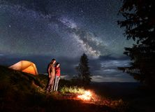 Man and woman are standing by campsite and looking at bonfire under the starry sky. Man and women tourists are standing by the campsite and orange tent, looking royalty free stock photo