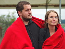 Man and women under a red blanket. Stock Images