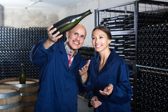 Man and women winemakers with wine bottle Royalty Free Stock Photography