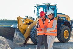 Man and woman worker on construction site. Man and women worker on construction site talking stock images
