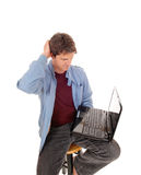 Man is wondering what is on the laptop. Stock Image
