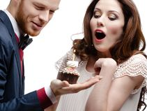 Man wonders his girlfriend with birthday pie. Man wonders his pretty girlfriend with birthday pie, isolated on white Royalty Free Stock Photo