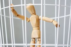 Man of wood in a cage royalty free stock photography
