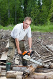 The man in wood saws a tree a chain saw Royalty Free Stock Images