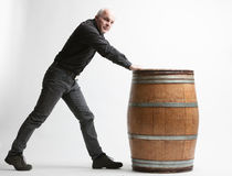 Man with wooden barrel. Man in dark casual clothes holding old wooden barrel by the edge, standing towards it, turning his head at camera. Isolated on white royalty free stock image