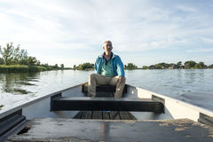 Man in wooden boat on the lake Royalty Free Stock Images