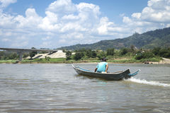 Man on wooden fishing boat on the river Stock Photos