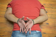 Man on wooden floor with handcuffs royalty free stock photography