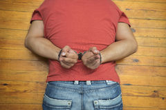 Man on wooden floor with handcuffs Stock Photos