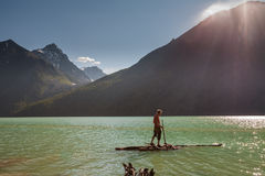 Man on wooden raft tries to cross the lake Royalty Free Stock Photos