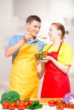 a man with a wooden spoon and a girl with a bowl of salad try the food cooked together stock images