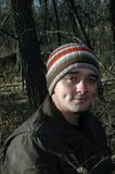 Man in woods. Young man hiking in the woods wearing striped knit cap Stock Image