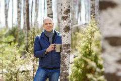 Man in woods collecting birch sap Stock Photo