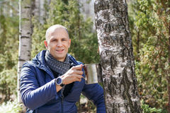 Man in woods collecting birch sap to steel mug Stock Photos
