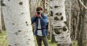 Man in woods looking and shoot photos in camera.Following side.Real people Millennial traveller backpacker adult male