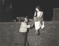 Man wooing woman sitting on brick wall Royalty Free Stock Photography