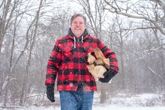 Man in wool jacket covered in snow bringing in firewood. Adult man in wool jacket covered in snow bringing in firewood on a cold winter day royalty free stock photos