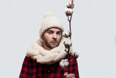 Man in a woolen scarf and hat is holding a cotton branch  on grey background Stock Photo