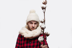 Man in a woolen scarf and hat is holding a cotton branch  on white background with copy space Stock Photo