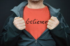 A man with the word believer on his red t-shirt. Man showing his t-shirt with the word BELIEVER written on it royalty free stock image