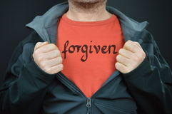 A man with the word forgiven on his t-shirt. Man showing his t-shirt with the word FORGIVEN written on it stock image