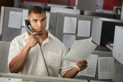 Man At Work. Serious office worker on a phone call with documents in his hand Stock Photos