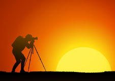 The man work with the camera on a background of the sun. Man work with the camera on a background of the sun Royalty Free Stock Photography