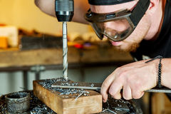Man in work on electric drill press Royalty Free Stock Photography