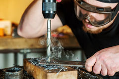Man in work on electric drill press Royalty Free Stock Photos