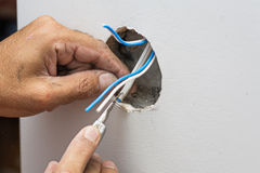 Man work with electric wires in hole of wall Stock Photography