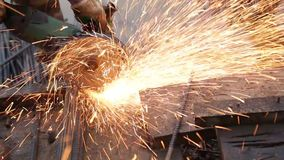 Worker cutting rebar with angle grinder. A worker cutting rebar with an angle grinder in a workshop stock video footage