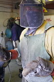 Man at work in the Foundry wearing protective gear. Man wearing protective gear working in the foundry. Head face body protection Stock Photo