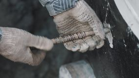 Man in work gloves and striped jacket untwist piece of metal rod from concrete stock video