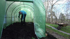 Man work hard with shovel and dig compost in greenhouse. stock footage