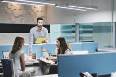 Man At Work Ignored by Female Colleagues In Coworking Space. Hispanic male employee in modern coworking space, excluded by female colleagues. Adult businessman stock photos