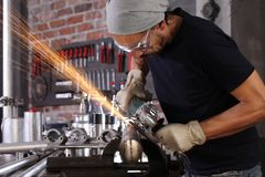 Free Man Work In Home Workshop Garage With Angle Grinder, Goggles And Construction Gloves, Sanding Metal Makes Sparks Closeup, Diy And Royalty Free Stock Images - 163104679