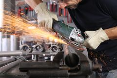 Free Man Work In Home Workshop Garage With Angle Grinder, Goggles And Construction Gloves, Sanding Metal Makes Sparks Closeup, Diy And Royalty Free Stock Photo - 163105475
