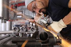 Free Man Work In Home Workshop Garage With Angle Grinder, Goggles And Construction Gloves, Sanding Metal Makes Sparks Closeup, Diy And Stock Photo - 163106380