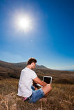 Man work on laptop in the mountains Stock Photography